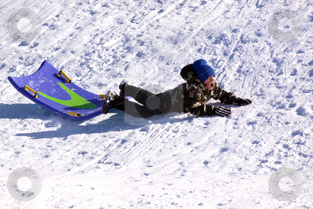 Little Boy Sledding down the Hill stock photo, Little Boy Falling While Sledding down the Hill - Winter Scenes by Mehmet Dilsiz
