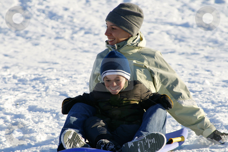 Happy Mother and Son Sledding down the Hill stock photo, Winter Scenes by Mehmet Dilsiz