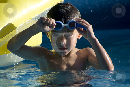 Little Boy in the Swimming Pool stock photo, Little boy taking his goggles off in the swimming pool by Mehmet Dilsiz