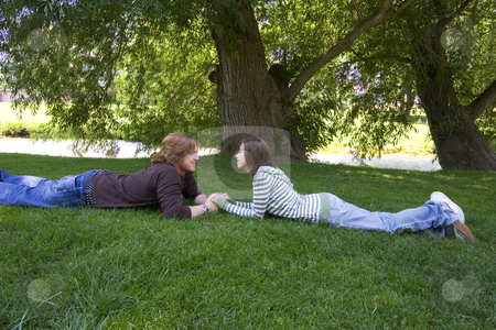 Young couple looking at each other at the Park stock photo, Young Married Couple laying down looking at each other in the park by Mehmet Dilsiz