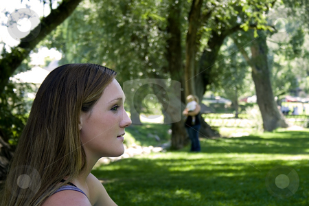 Beautiful Girl in the Park Looking into the Future stock photo, Girl Sitting in the Park Looking into the Future of Motherhood by Mehmet Dilsiz