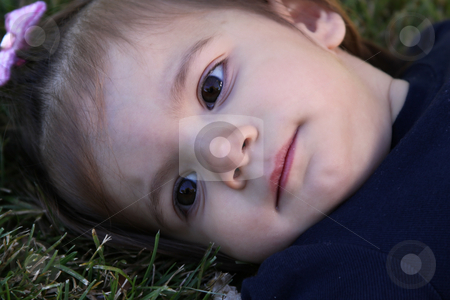 Close up on a Cute Girl stock photo, Close up on a Cute Little Girl Laying Down on the Grass by Mehmet Dilsiz