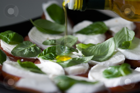 Mozzarella and tomato stock photo, Close-up of olive oil being poured on mozzarella and tomato dish by Dominik Gajerski