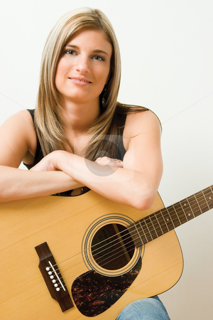 Women with accoustic guitar stock photo, Thirty something women sitting on stule leaning on accoustic guitar by Yann Poirier