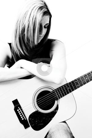 Women with accoustic guitar stock photo, Thirty something women sitting on stule leaning on accoustic guitar looking down by Yann Poirier