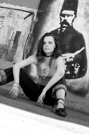 Urban girl stock photo, Twenty something urban fashion sitting in front of a graffitti wall by Yann Poirier