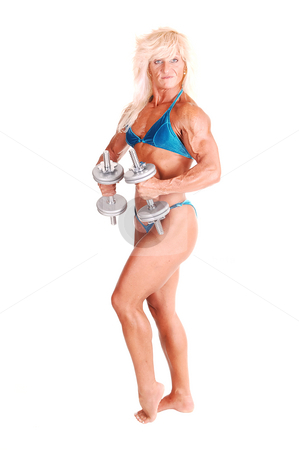 Bodybuilding woman. stock photo, A strong blond woman in an blue bikini standing bare foot in the studio with dumbbells and shooing her muscular body and bicep, over white. by Horst Petzold