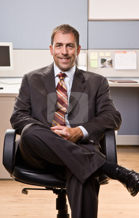 Businessman smiling sitting in chair stock photo, Businessman smiling sitting in chair by Jonathan Ross