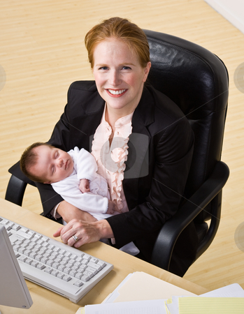 Businesswoman holding baby at desk stock photo, Businesswoman holding baby at desk by Jonathan Ross