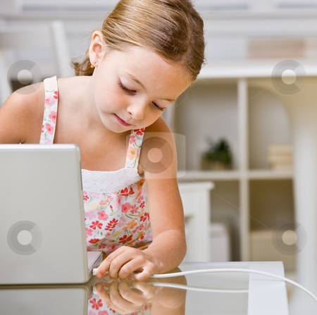 Girl plugging internet cable into laptop stock photo, Girl plugging internet cable into laptop by Jonathan Ross