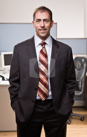 Businessman smiling with hands in pockets stock photo, Businessman smiling with hands in pockets by Jonathan Ross