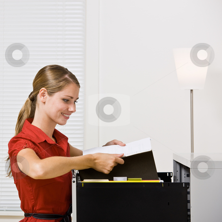 Businesswoman putting file in file cabinet stock photo, Businesswoman putting file in file cabinet by Jonathan Ross