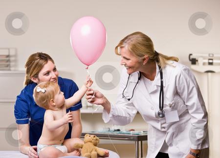 Doctor handing baby girl balloon stock photo, Doctor handing baby girl balloon by Jonathan Ross
