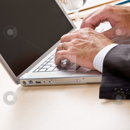Close up of businessman typing on laptop stock photo, Close up of businessman typing on laptop by Jonathan Ross