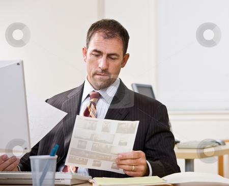 Businessman reviewing paperwork stock photo, Businessman reviewing paperwork by Jonathan Ross