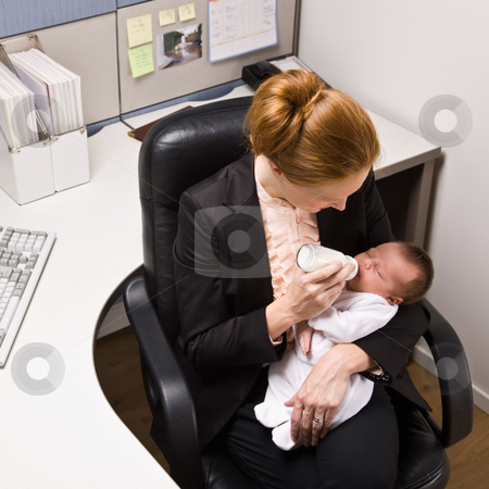 Businesswoman feeding baby at desk stock photo, Businesswoman feeding baby at desk by Jonathan Ross