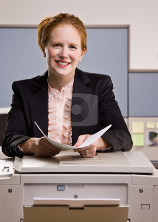 Businesswoman copying papers in office stock photo, Businesswoman copying papers in office by Jonathan Ross