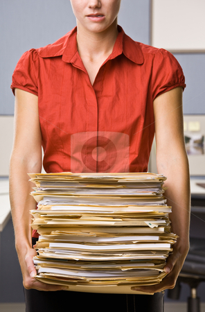 Businesswoman carrying stack of file folders stock photo, Businesswoman carrying stack of file folders by Jonathan Ross