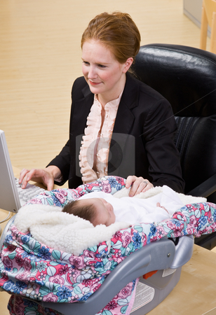 Businesswoman working with baby at desk stock photo, Businesswoman working with baby at desk by Jonathan Ross