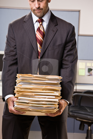 Businessman carrying stack of file folders stock photo, Businessman carrying stack of file folders by Jonathan Ross