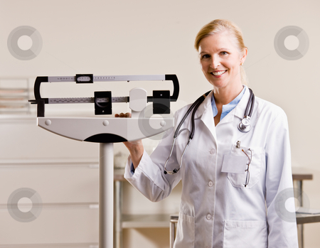 Doctor standing with weighing scales stock photo, Doctor standing with weighing scales by Jonathan Ross