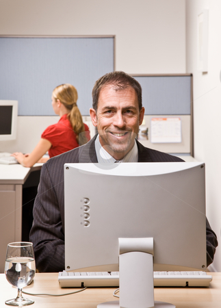 Businessman typing on computer at desk stock photo, Businessman typing on computer at desk by Jonathan Ross