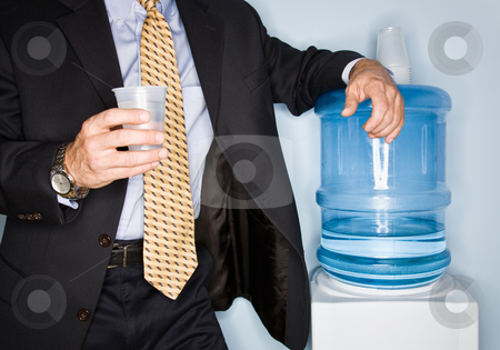 Businessman drinking water from water cooler stock photo, Businessman drinking water from water cooler by Jonathan Ross
