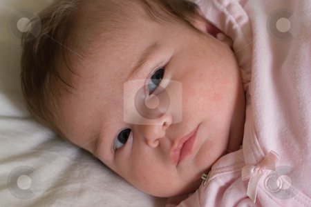 Serious baby girl stock photo, One month baby with a serious expression looking in the distance by Yann Poirier