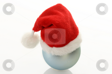 Santa claus cap stock photo, Christmas ball with santa claus cap  on bright background. Shot in studio. by Birgit Reitz-Hofmann