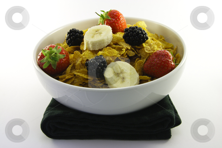 Cornflakes and Fruit in a White Bowl stock photo, Cornflakes with strawberries, blackberries and banana in a round white bowl with a black napkin on a white background by Keith Wilson