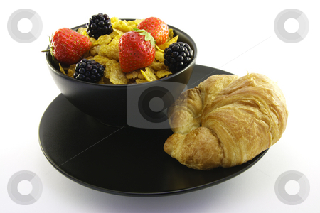 Cornflakes in a Black Bowl with a Croissant stock photo, Cornflakes with strawberries and blackberries in a round black bowl with a croissant on a white background by Keith Wilson