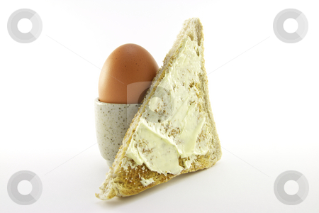 Lightly Boiled Egg and Toast stock photo, Lightly boiled egg in an egg cup with a slice of buttered toast on a white background by Keith Wilson