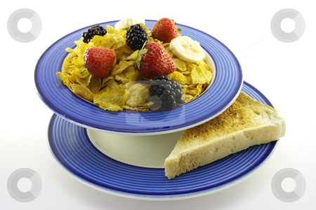 Cornflakes and Fruit with Toast stock photo, Cornflakes with strawberries, blackberries and banana in a round blue bowl with a slice of toast on a plate with a white background by Keith Wilson
