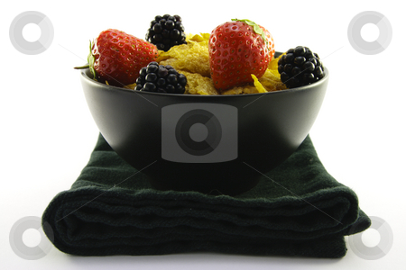 Cornflakes and Fruit in a Black Bowl stock photo, Cornflakes with strawberries and blackberries in a round black bowl with a black napkin on a white background by Keith Wilson
