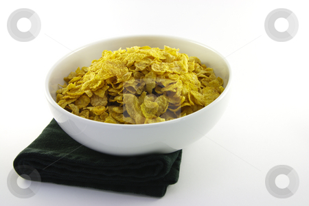 Cornflakes in a Bowl stock photo, Golden crisp cornflakes in a round white bowl with a black napkin on a white background by Keith Wilson