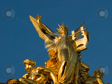 Golden sculpture on the top of the Opera Garnier stock photo, Opera Garnier, Paris, France, Sculptural detail on the roof of the Opera Garnier, Paris, 2007 - Closeup of a golden statue of a female angel holding a Harp surrounded with two others angels.  This statue is at the top of the Palais Garnier, also known as the Op? by FEL Yannick