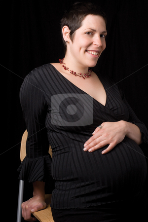 Pregnant Women stock photo, Sitting portrait of a late twenty pregnant women with a big smile by Yann Poirier