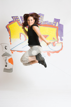 B Girl Jumping stock photo, Late twentie hip hop women dancer, B Girl, in mid jump in front of a graffiti background by Yann Poirier