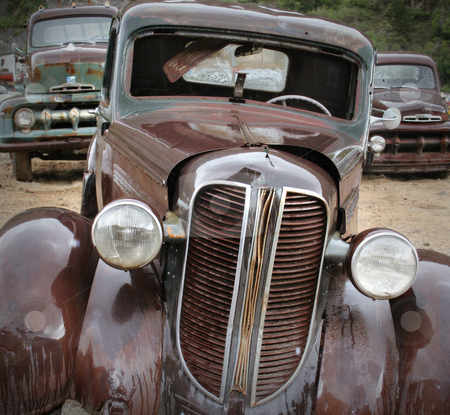 Rusting Cars and Truck at the Junkyard in Rain stock photo, Old rusted cars in the rain at the junkyard looking sad. Good for themes of transportation, retirement, change, aging, retro, nostalgia, memories, family, friendship, humor. by Jeff DeMent