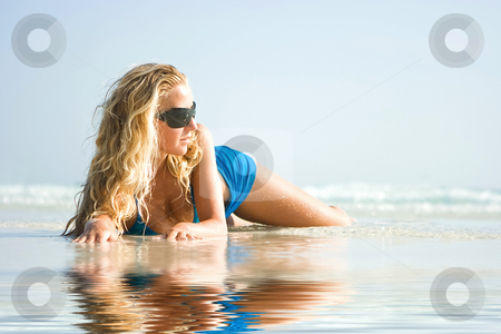 Girl on beach with reflection in water stock photo, Blond girl in sunglasses lying on the beach with reflection in water by Dmitry Rostovtsev