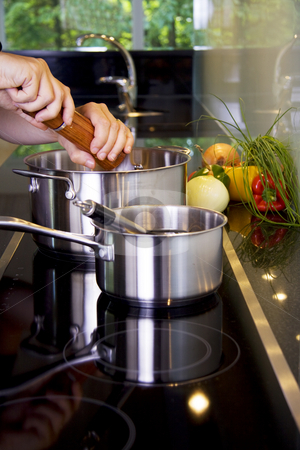 Chef preparing a meal stock photo, Chef adding pepper using a grinder while cooking in a modern kitchen by Daniel Kafer