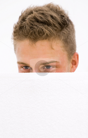 Young man hiding stock photo, Young man hiding himself behind a white towel by Karin Claus