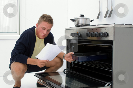 Young man clueless in kitchen stock photo, Young man clueless in kitchen reading from recipe by Karin Claus