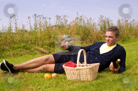 Young man ready for picnic stock photo, Young man laying down in the grass ready for picnic by Karin Claus