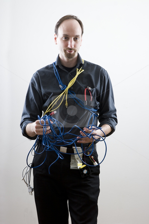 Listening to problem stock photo, Computer technician looking exaperated holding network cable by Yann Poirier