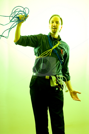 Singing Technician stock photo, Computer technician, wearing many different kind of cables and wires, holding on to a network cable in the middle of a song by Yann Poirier