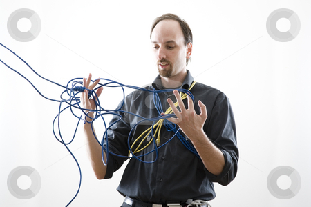 Confuse technician stock photo, Computer technician looking confuse trying to untie network cable by Yann Poirier