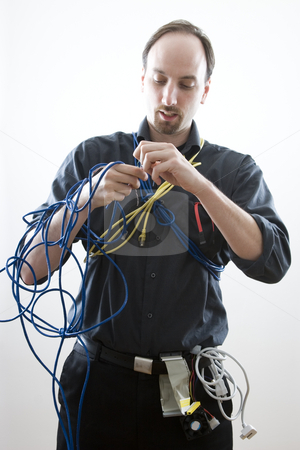 Stuck in wires stock photo, Computer technician trying to figure wires by Yann Poirier