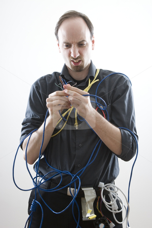Clueless technician stock photo, A clueless network technician looking at wires by Yann Poirier