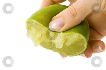 Hand squeezing green lime stock photo, Female hand squeezing juice from a green lime. Isolated on white background. by Natalia Banegas